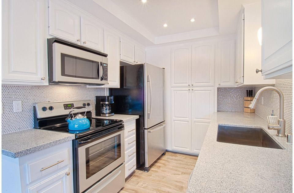 Stylish penny-tile backsplash & granite counter complete this chef's delight!