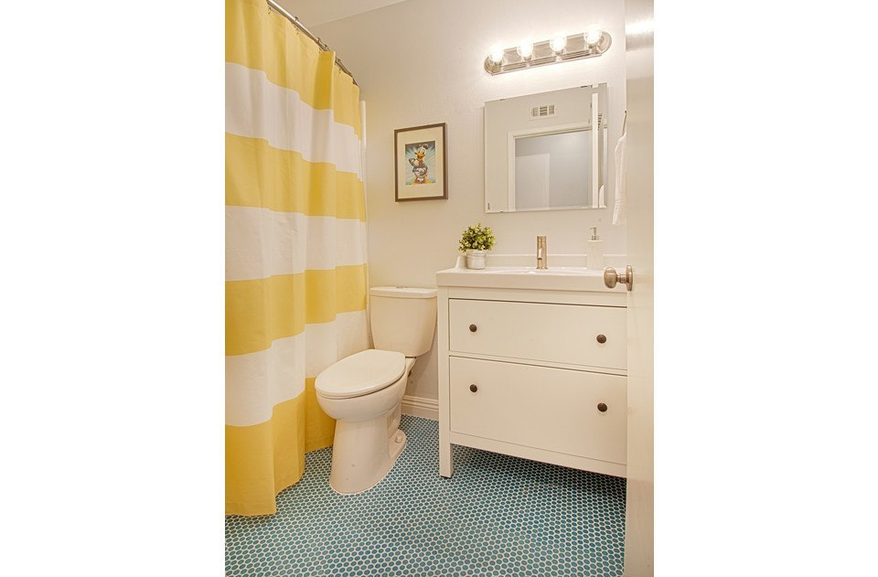 Donald duck bathroom with retro blue penny-tile floors and sparkling white tub.