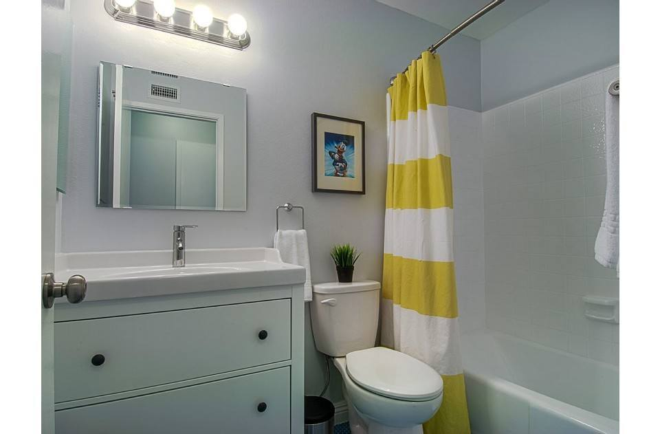 Upstairs bath with tub/shower, blue penny tile floors & plush white towels