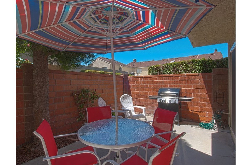 Outdoor patio with gas grill, dining table and umbrella