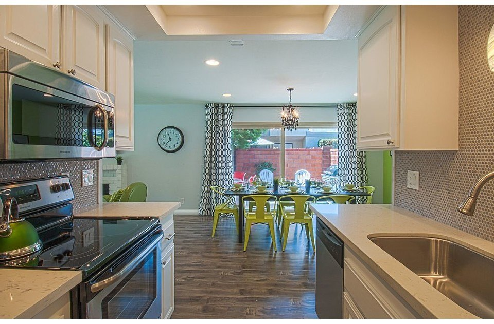 Remodeled kitchen with stainless appliances, quartz counters, and fun penny tile
