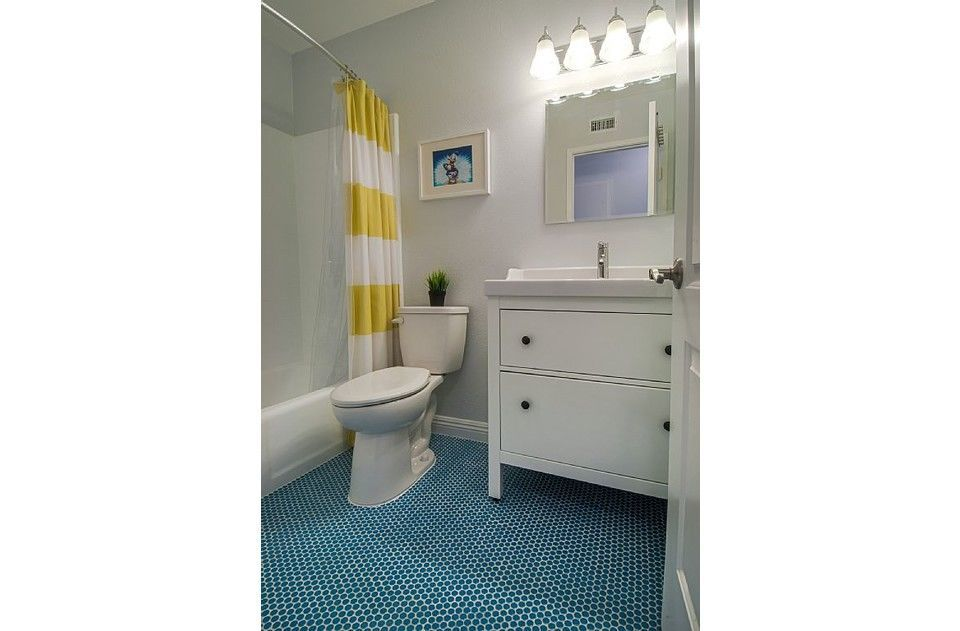 Upstairs hall bath with fun penny tile floor & sparkling white tub and shower.