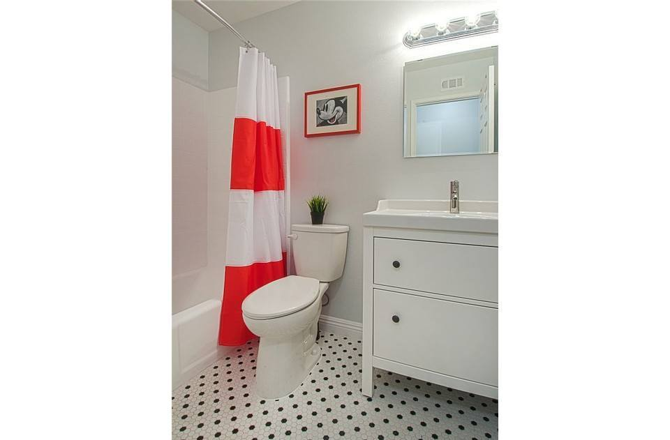 Hall bath with sparkling white tub/shower. Black and white floor tiles.