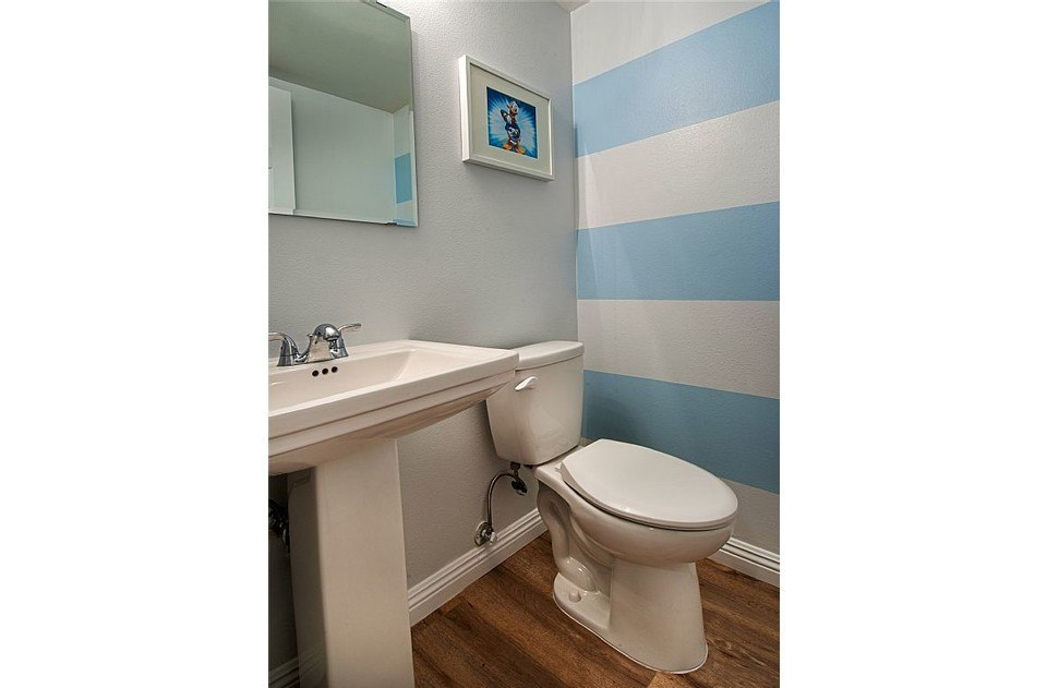 Downstairs half bath with fun stripes. New fixtures in all bathrooms.