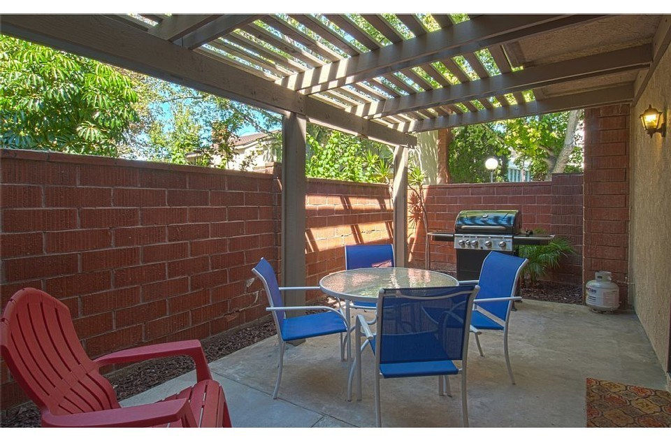 Side patio stays cool in the shade. Fire up the grill and enjoy an outdoor meal.
