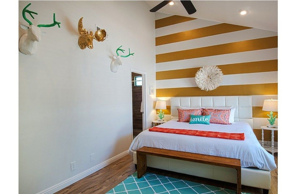 Fun decor with faux animal heads, coral lamps, gold stripes. Bright and fun!