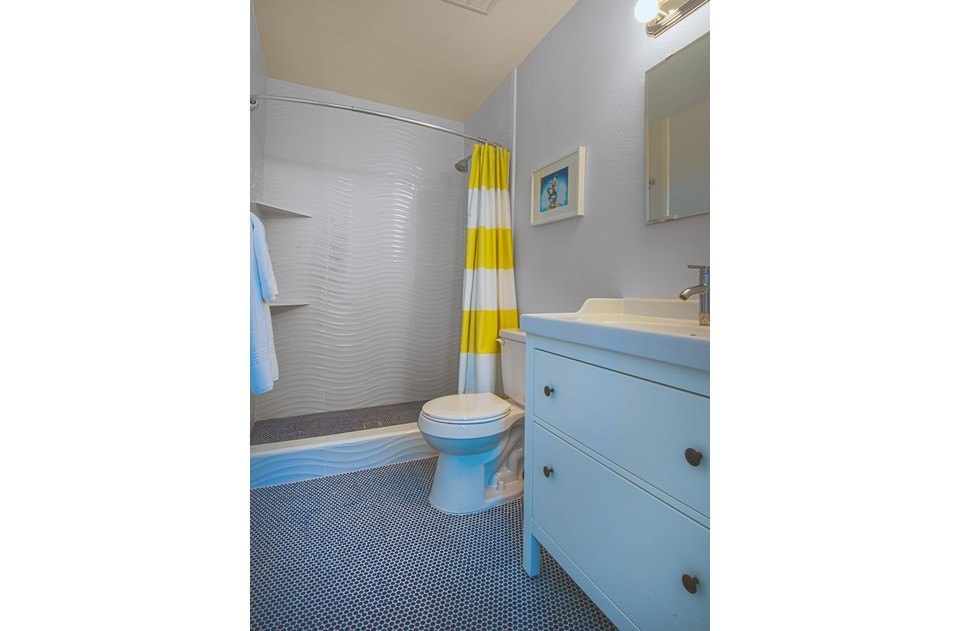 Master bath with fun blue penny tile and custom wave extra tall shower.