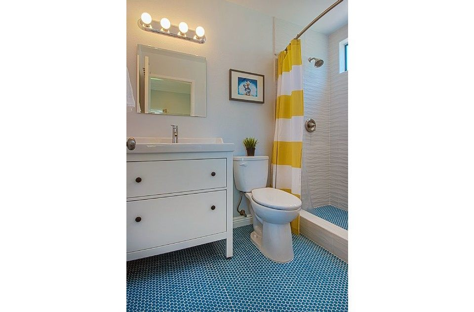 Stunning 3D 'wave' tile and retro blue penny tile floor in master bath.