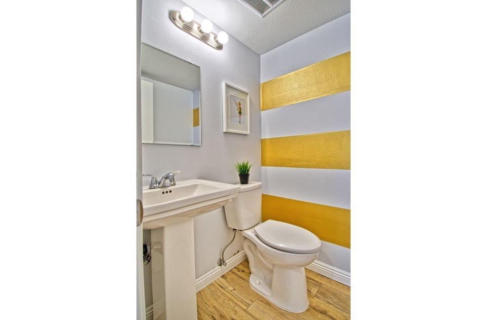 Downstairs half bath with gorgeous gold stripes. New fixtures in all bathrooms.