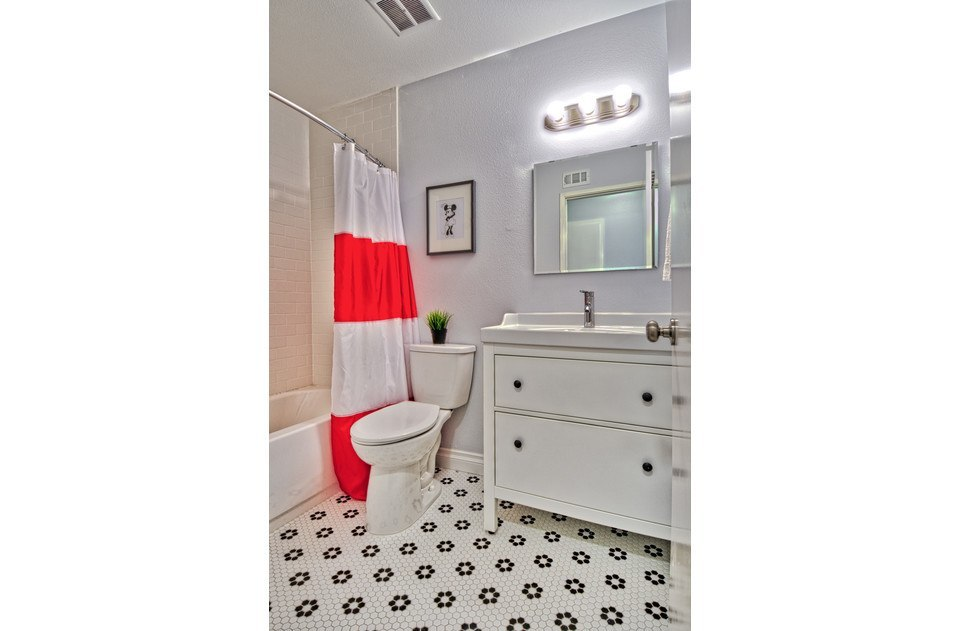 Minne inspired hall bath with sparkling white tub/shower.