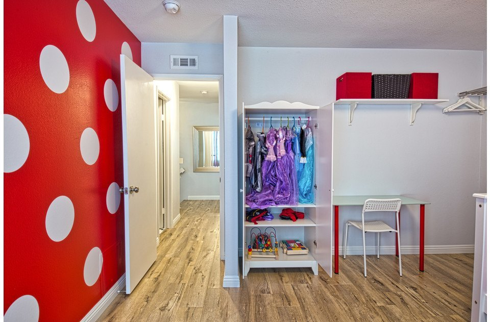 Kid's room complete with polka dot wall, toys and costumes for playing dress up!